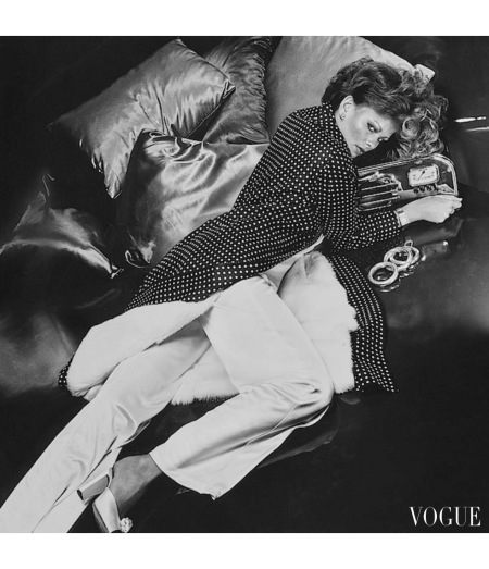 Regine Jaffrey Model, lying next to a radio, wearing a black and white polka dot silk satin robe with a detachable white rabbit lining by Ritter Bros. and Ben Thylan Vogue Nov 1974 © Ch
