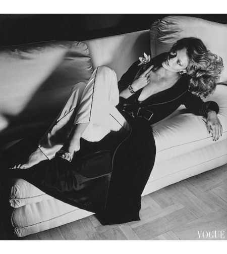 Regine Jaffrey, reclining on a sofa with legs crossed, and wearing a black velvet robe with quilted satin cuffs and contrast piping, and light silk satin pants with thin black seam strip