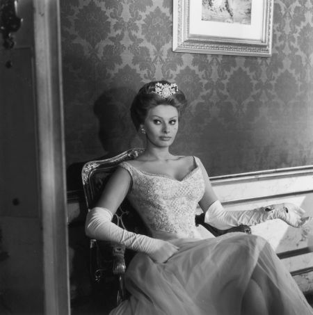 Sophia Loren wears a ball gown, long white gloves, and a tiara while sitting in an armchair on the set of director Michael Curtiz's film, 'A Breath of Scandal'