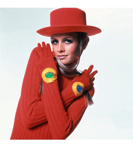 Twiggy in red ribbed wool chenille cropped jumpsuit by Pattie Tuttman for Silverworm with a watch on each wrist, both by Crocker; Hansen gloves and a Amish felt hat by Tally H Vogue Nov