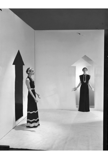Two models, standing in a white room with arrows painted on walls and wearing dresses by Schiaparelli; Left in a dark crepe with bands of gold braids down the front, over satin pajamas;