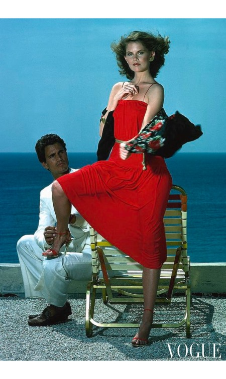 A model wearing a red dress with a man wearing white Vogue June 1977 © Guy Le Baube