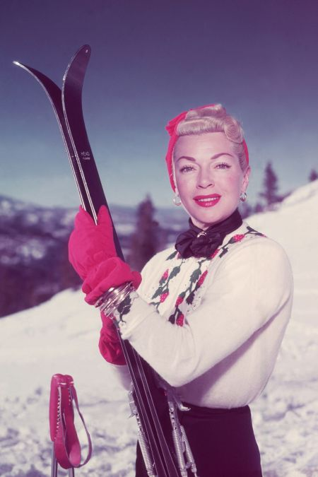 Lana Turner (1921- 1995), wearing a skiing outfit consisting of a turban, gloves, a knit sweater and ski pants, holding skis on a snowy ski slope. 1955 (Photo by Hulton Archive:Getty Im