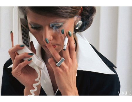 Regine Jaffry wearing Revlon nail polish smoking while using a telephone Vogue May 1975 © Kourken