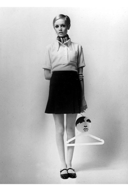 Twiggy stands wearing a yellow shirt, scarf and mini skirt and flat Mary Jane shoes whilst holding a coat hanger bearing her image in 1967. (Photo by Popperfoto:Getty Images) b