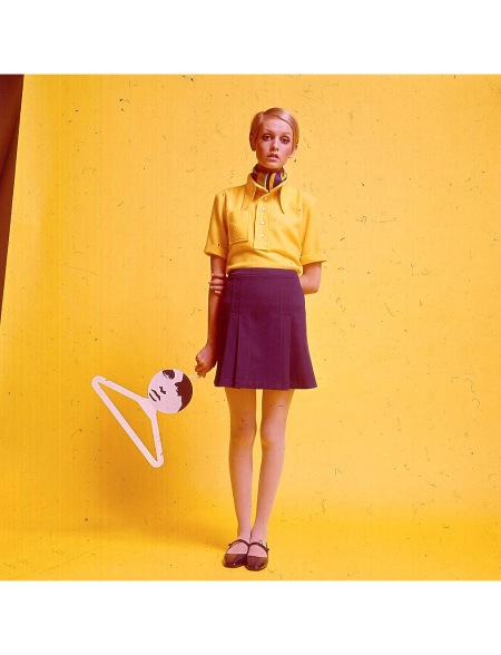 Twiggy stands wearing a yellow shirt, scarf and mini skirt and flat Mary Jane shoes whilst holding a coat hanger bearing her image in 1967. (Photo by Popperfoto:Getty Images)