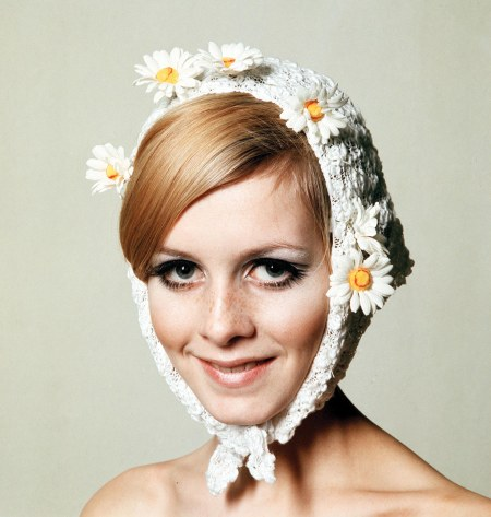 1966. A facial portrait of model Twiggy wearing a fashionable and quirky white bonnet hat which has daisies attached and also wraps round her chin, whilst she smiling at the camera.