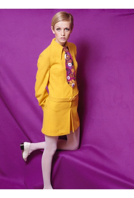 Twiggy wearing a fashionable yellow collared outfit with a multi-coloured floral tie, posing for the camera in a studio against a brightly coloured purple backdrop 1967 (Photo by Popperf