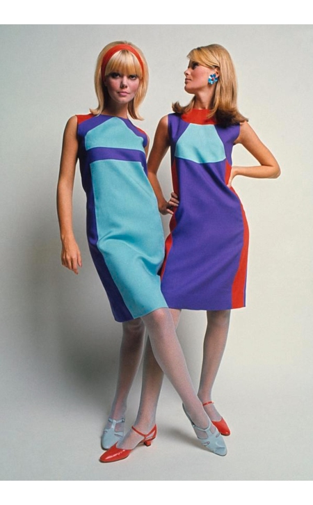 wo models wearing Robert Sloan A-line shift dresses with Christian Dior stockings, Sandor Goldberg flower earrings and, on the left, blue Divina t-strap shoes and, on the right, red Jant