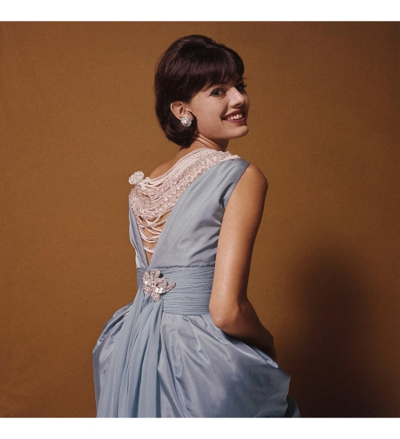 Woman looking over shoulder wearing blue dress which has a V shaped back, adorned with many strands of pearls in different sizes Glamour Sept 1960 © Bert Stern